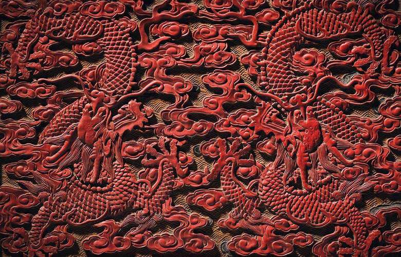 Two of the nine five-clawed dragons on the throne, finely carved in red lacquer