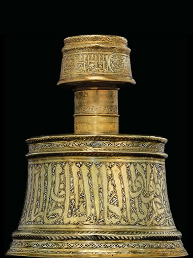 An important rasulid silver and copper-inlaid brass candlestick, Yemen, 14th century. 11⅝ in (29.5 cm) high. Sold for £182,500 on 8 October 2015 at Christie's in London