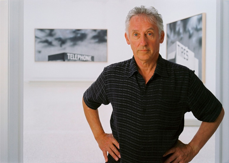 Ed Ruscha with two works shown at Venice Blue Collar Telephone, 1992. Acrylic on canvas. 54 x 120⅛ in (137.16 x 305.11 cm); and Blue Collar, 1992. Acrylic on canvas. 54 x 120 in (137.16 x 305 cm). © Ed Ruscha. Photography by Gary Regester. Courtesy of Ed Ruscha and Gagosian Gallery