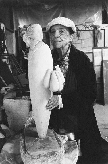 Louise Bourgeois in her Brooklyn studio in 1993 with her sculpture, WOMAN WITH PACKAGES, 1991-93. Photo by Vera Isler-Leiner © Artists Rights Society (ARS), NYProLitteris, Zurich. Artworks © The Easton FoundationVAGA at ARS, NY and DACS, London 2019