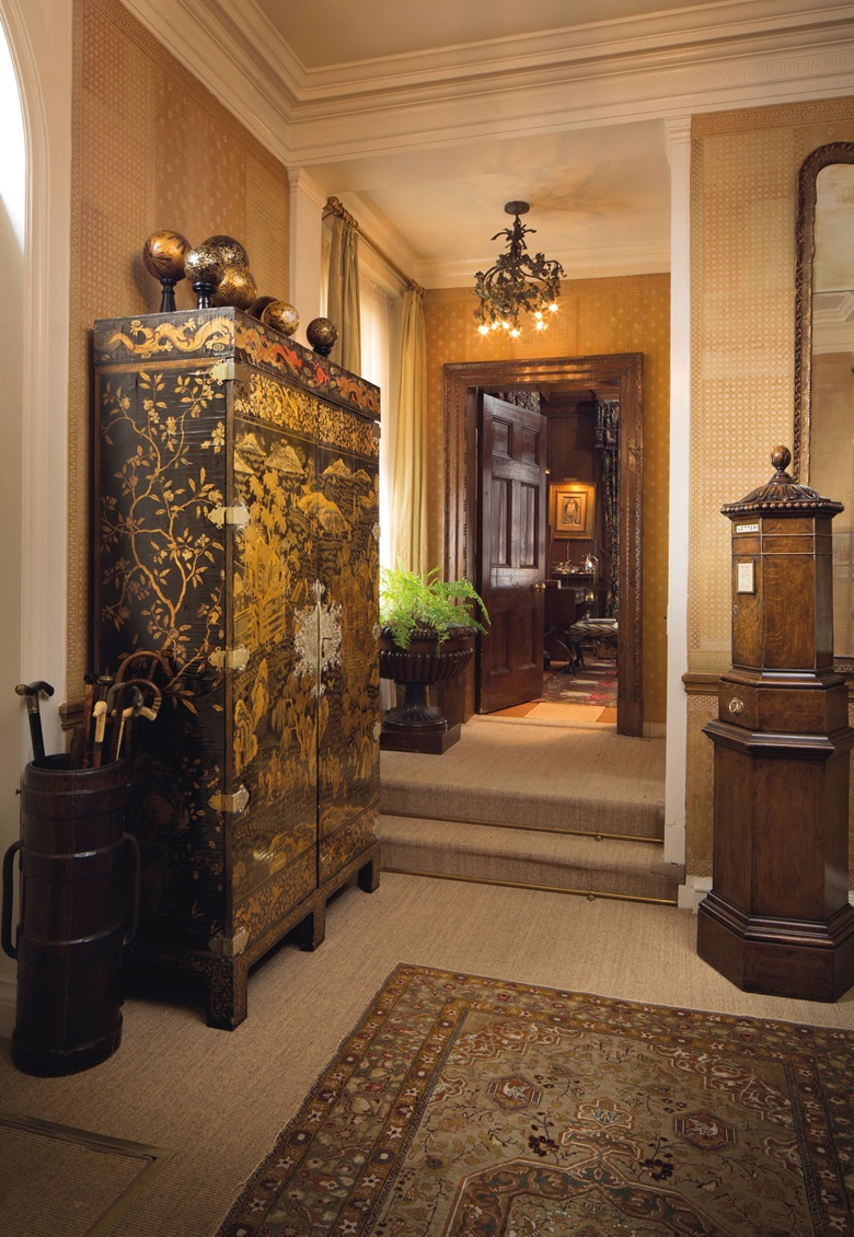 The entrance hall of the Heinzes New York townhouse. Including 16 parcel-gilt and black-painted wooden spheres, second half 20th century. Estimate £1,000-1,500. A Victorian brass-mounted oak 'country house' penfold letter box, By Walter Thornhill, circa 1870. Estimate £2,500-4,000. One of a pair of Chinese export black and gilt-lacquer cabinets, Late 19th