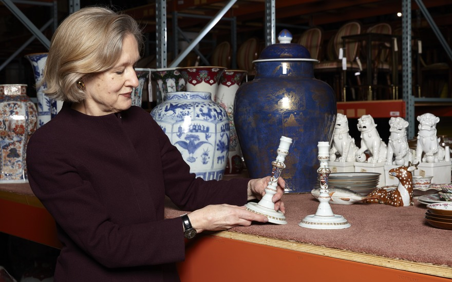 Specialist Becky MacGuire with a pair of Chinese export candlesticks with the arms of Philip V of Spain, circa 1725-30. 7¾ in (19.7 cm) high