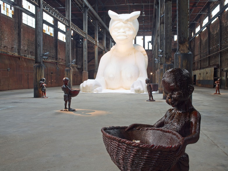 Kara Walker (b. 1969), At the behest of Creative Time Kara E. Walker has confected A Subtlety, or the Marvelous Sugar Baby, an Homage to the unpaid and overworked Artisans who have refined our Sweet tastes from the cane fields to the Kitchens of the New World on the Occasion of the demolition of the Domino Sugar Refining Plant. A project of Creative Time. Domino Sugar Refinery, Brooklyn, NY, May