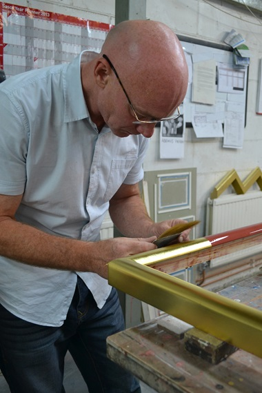 Gilder applying gold leaf to gesso frame. © John Jones London