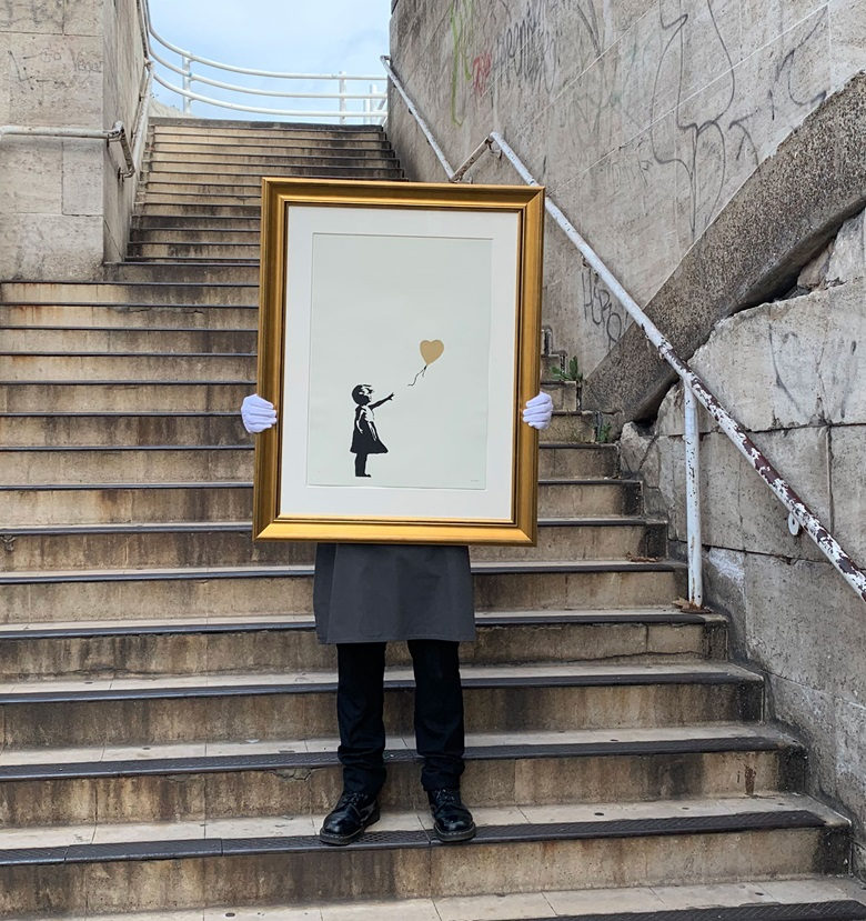 Banksy (b. 1975), Girl with Balloon - Colour AP (Gold), 2004. Screenprint in black and gold, signed. Image 390 x 260 mm, sheet 695 x 495 mm. Estimate £150,000–250,000. Offered in Banksy I cant believe you Morons actually buy this sht, 11-24 September, Online. Artwork Courtesy of Pest Control Office