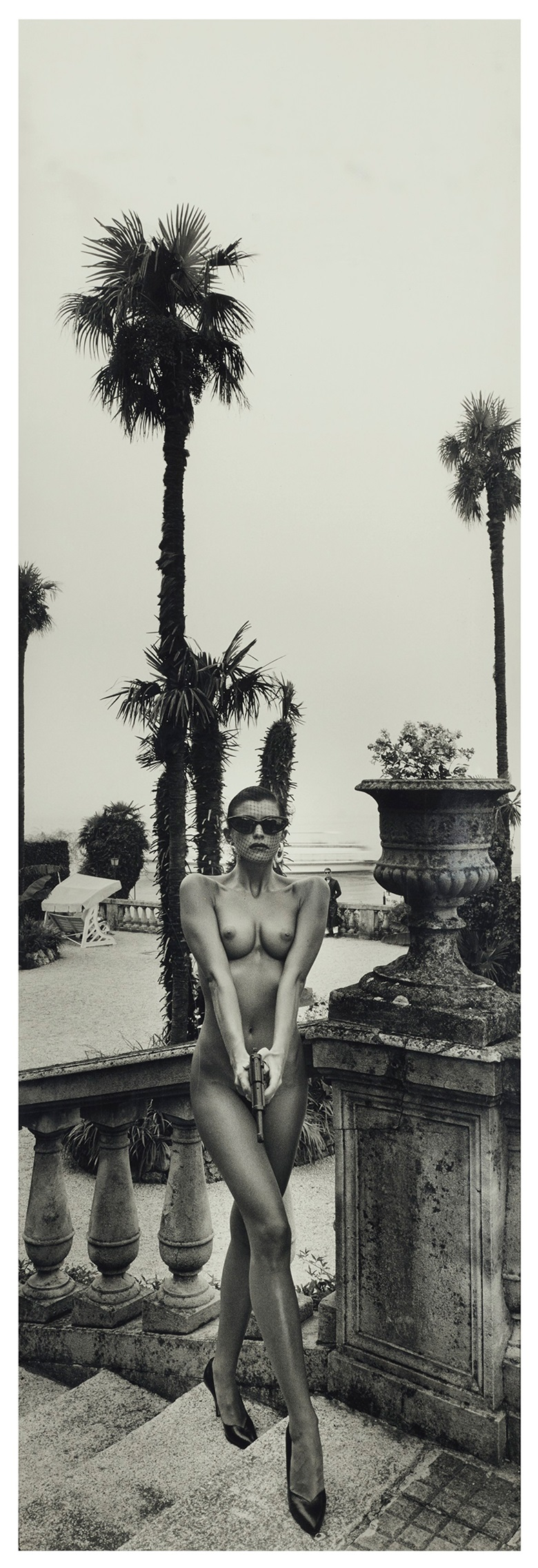 Helmut Newton (1920-2004), Panoramic Nude, Woman with Gun, Villa d'Este, Como, 1989. Gelatin silver print. Sheet 61½ x 22 in (158.8 x 55.9 cm). Estimate $300,000-500,000. Offered in Photographs on 2 October 2019 at Christie's in New York