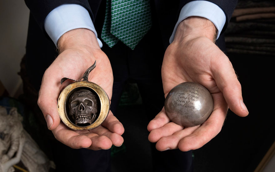 Specialist Milo Dickinson holds a rare 17th-century silver apple with bite marks that opens up to reveal a pomander in the shape of a skull, 1628. Diameter of apple 2⅜ in (6 cm); height of skull