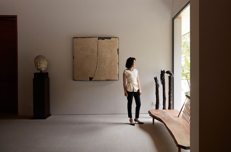 Erica Lai in her Singapore home with Su Xiaobai, A Calyx-shaped Cloud No. 1, 2012, which hangs next to a Northern Qi marble Buddha head. Artwork Su Xiaobai, A Calyx-shaped Cloud No. 1, 2012. Courtesy the artist and Pearl Lam Galleries