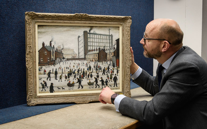 Nick Orchard, Head of Modern British & Irish Art at Christie's, with L.S. Lowry's The Mill, Pendlebury (1943), offered in London on 21 January. Artwork © The Estate of