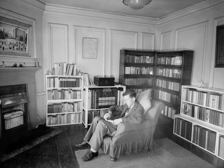 Leonard D. Hamilton in his room at the University of Oxford, with the Lowry painting hanging above the fireplace. Artwork © The Estate of L.S. Lowry. All Rights Reserved, DACS 2020