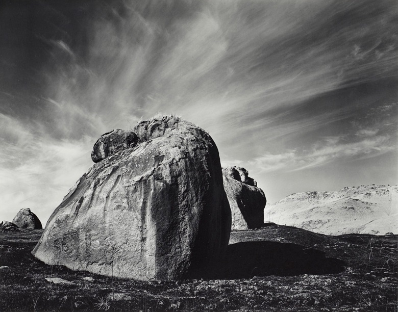 Ansel Adams (1902–1984), Rocks and Clouds, Sierra Nevada Foothills, California, 1938. Gelatin silver print, mounted on board, printed 1979, signed in pencil (mount, recto); titled and dated in ink in photographers Carmel credit stamp (mount, verso). Mount 15⅞ x 19⅞ in (40.3 x 50.5 cm). Estimate $8,000-$12,000. Offered in Ansel Adams and the American West Photographs from the Center for Creative