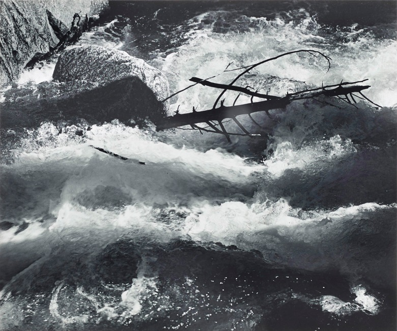 Ansel Adams (1902–1984), Rushing Water, Merced River, Yosemite National Park, California, c. 1955. Gelatin silver print, mounted on board signed in ink (mount, recto). Mount 13⅞ x 17⅞ in (35.4 x 45.4 cm). Estimate $4,000-6,000. Offered in Ansel Adams and the American West Photographs from the Center for Creative Photography, 24 March–2 April 2020, Online. Artwork © The Ansel Adams