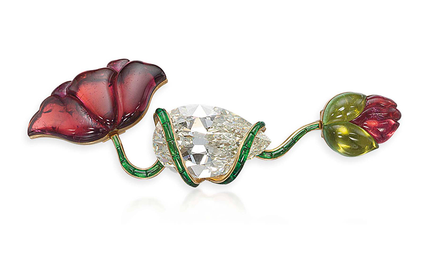 A tourmaline and diamond flower brooch, by JAR. Designed as two green and pink tourmaline poppy flowerhead and bud, linked by a green tourmaline scrolling stem centering upon a pear-shaped diamond.