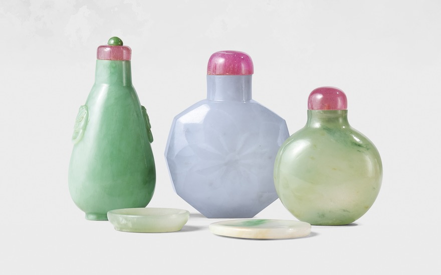 From left A jadeite 'mask handle' snuff bottle, probably imperial, Qing dynasty, 1760-1850. Bottle 2⅗  in (6.9  cm) high, tourmaline stopper, dish 1⅛ in (2.7  cm) long. Estimate