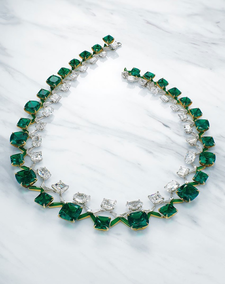 A Boghossian emerald and diamond double rivière. Twenty-eight cushion and octagonal-cut emeralds of 10.41 to 1.48 carats, twenty-two oval and rectangular-cut diamonds of 4.22 to 0.70 carats, vari-cut diamonds, fancy-cut jadeite, gold, inner circumference 40.0 cm, signed Boghossian, designed by Edmond Chin, white Boghossian case. Estimate HK$55,000,000-80,000,000. Offered in Magnificent