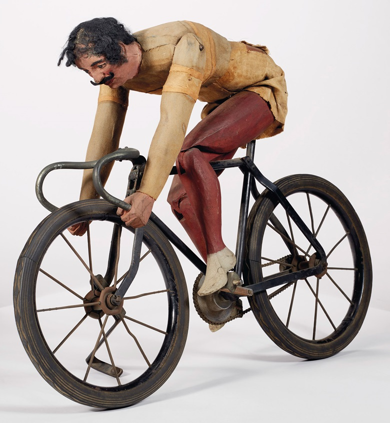 An articulated painted pine and fabric cyclist, probably New York City, early 20th century. 21¼ in long, 15½ in high, 4¾ in wide. Estimate $5,000-10,000. Offered in In Praise of America Important American Furniture, Folk Art, Silver, Prints and Broadsides on 22 January 2021 at Christie's in New York