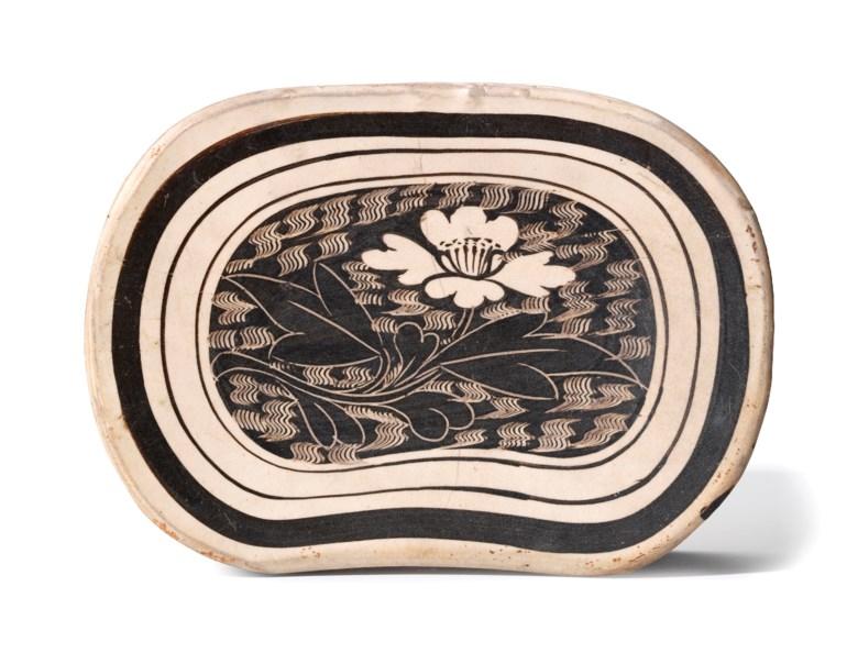 北宋 磁州窑白地剔黑莲纹枕。估价:40,000-80,000港元。佳士得香港于10月4至11日举行的「古今  网上拍卖」拍卖呈献此拍品。