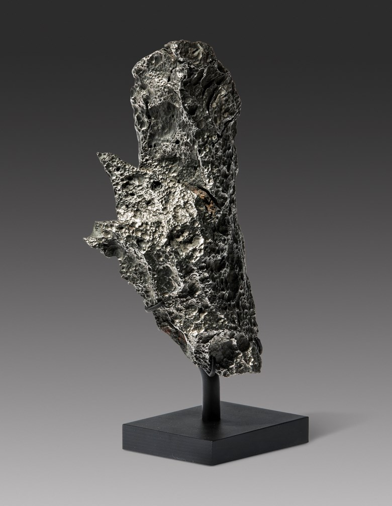 An Aesthetic Chinga Meteorite — Tabletop Sculpture from Outer Space, Iron, ungroupedChinge River, Russia. 9 x 3 x 3 in (23 x 7 x 7.5 cm) on stand. Estimate                    £5,000-8,000. This lot is offered in Sculpted by Nature Fossils, Minerals and Meteorites, 10-17 April 2018, Online