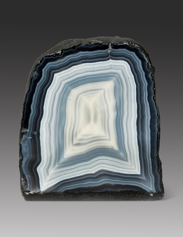 A rectangular specimen of banded agate, Southern Brazil. 10½ x 9 x 4 in (27 x 23 x 10 cm). Estimate                    £2,000-3,000. This lot is offered in Sculpted by Nature Fossils, Minerals and Meteorites, 10-17 April 2018, Online